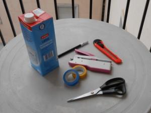 gli occorrenti sono cartone tetrapak nastro isolante colorato, forbici, spillatrice, tagliari taglierina, pennarello